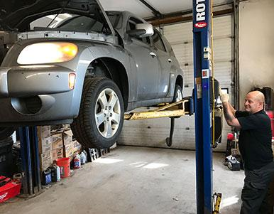 Employee operating car lift